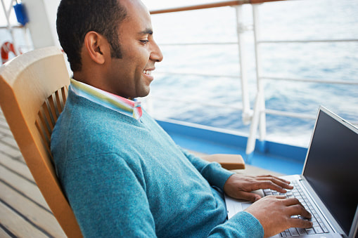 man using a laptop on a cruise ship deck, connected via Wi-Fi