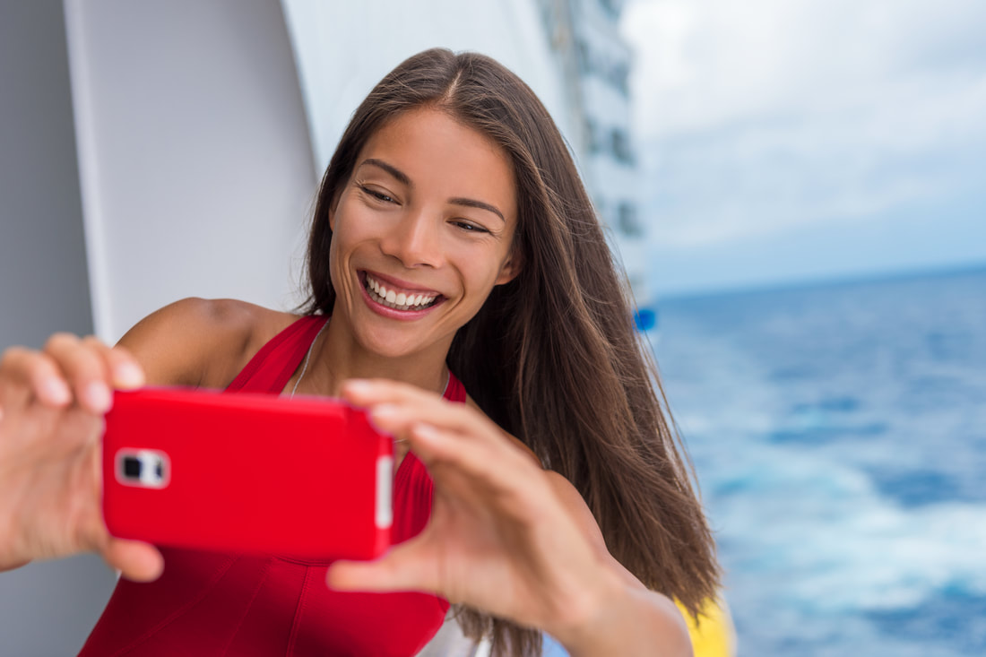 woman taking a selfie on a cruise ship deck while at sea