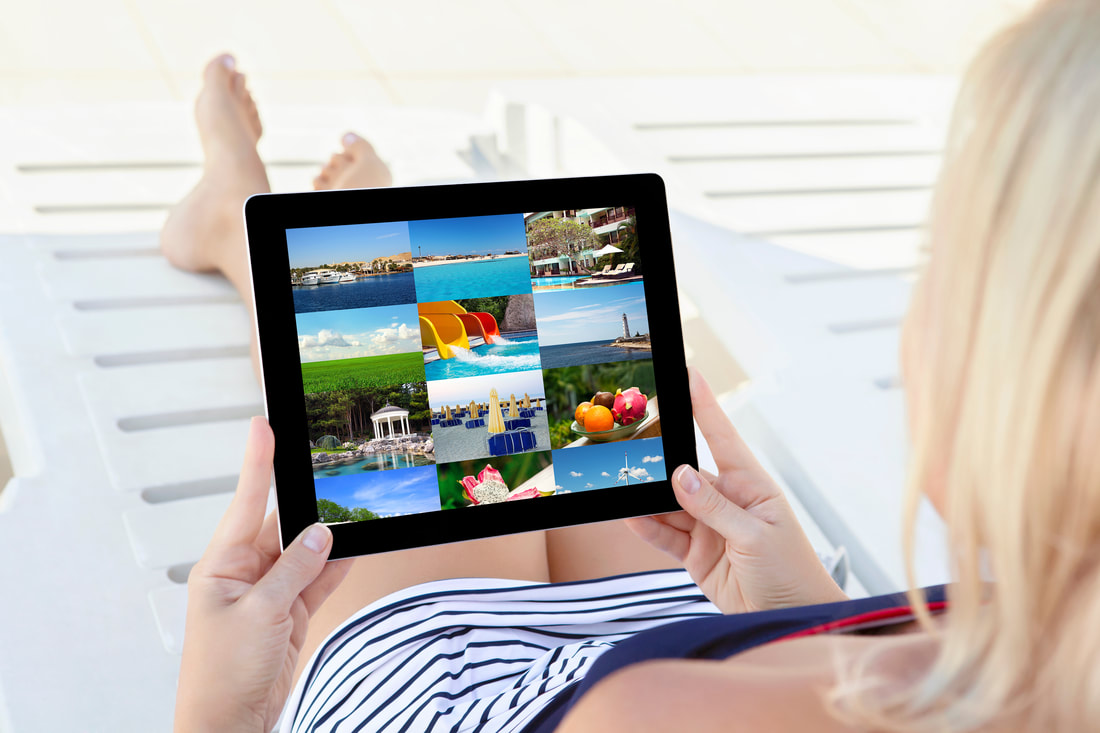 Woman sitting on pool deck chair scrolling through pictures on her cellular network connected tablet